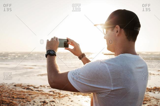 Man taking photo of sea sunset