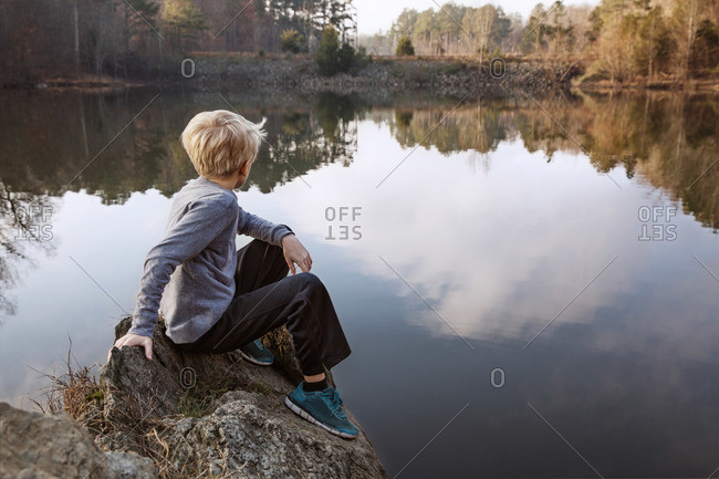Child sitting on lake edge, Raleigh