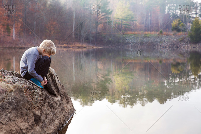 Child seated at lake rock, Raleigh