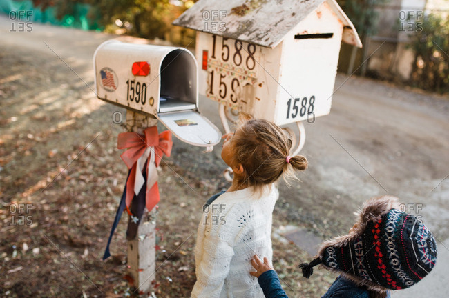 Two kids at a mailbox