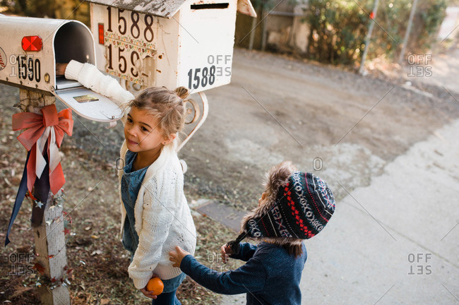 Two kids checking a mailbox