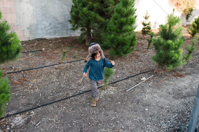 Kid carrying stick on a tree farm