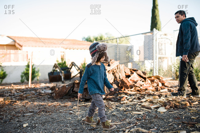 Child and man by chopped wood pile