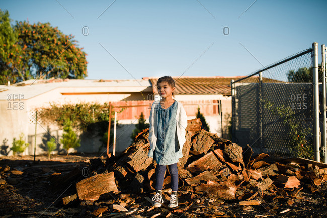 Girl by chopped wood pile
