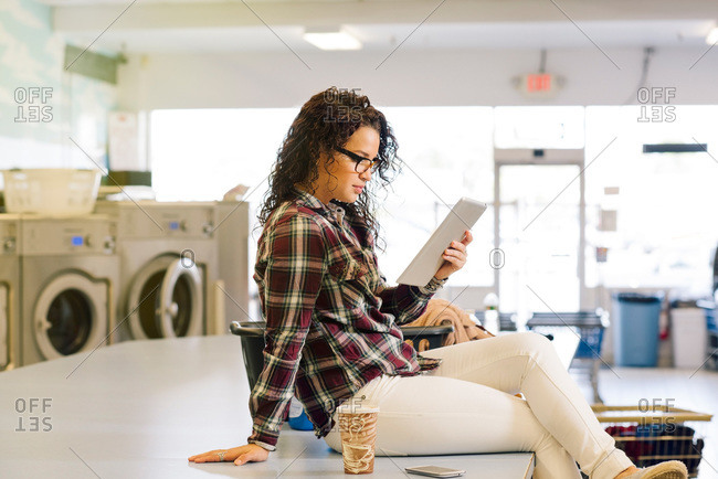 Woman with tablet in laundromat