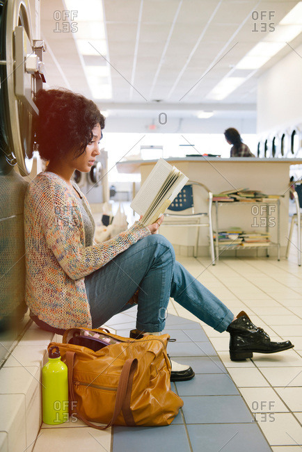Woman reading book in laundromat