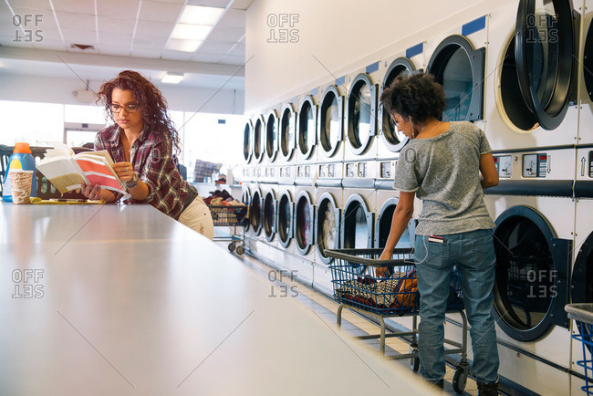 Woman reading a book in laundromat