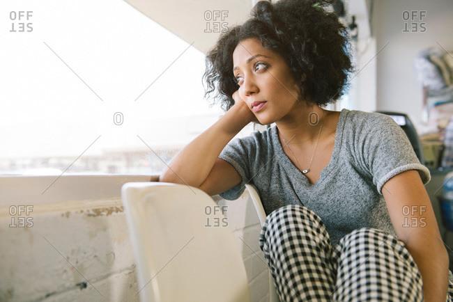 Woman gazing out laundromat window