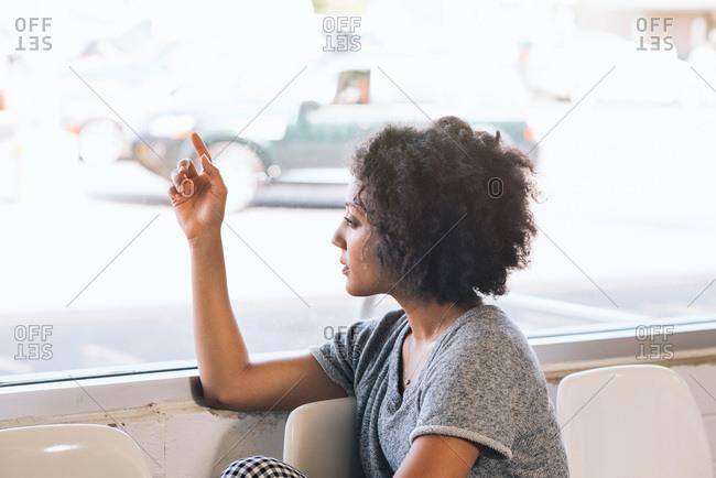 Woman staring out laundromat window