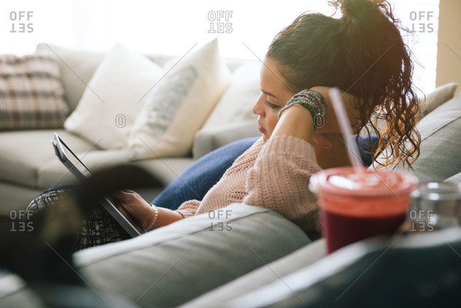Woman resting on couch with tablet