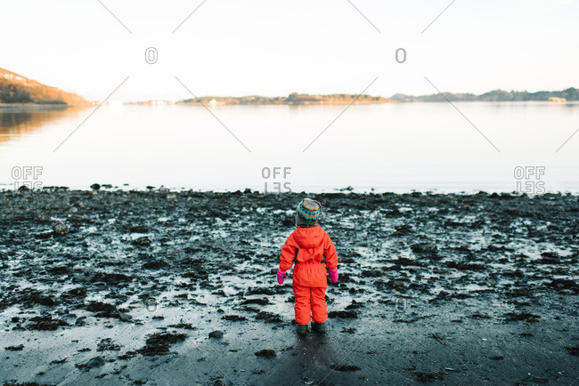 Young girl standing on a beach in winter