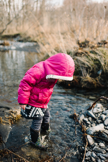 Young girl playing in a stream with winter boots on