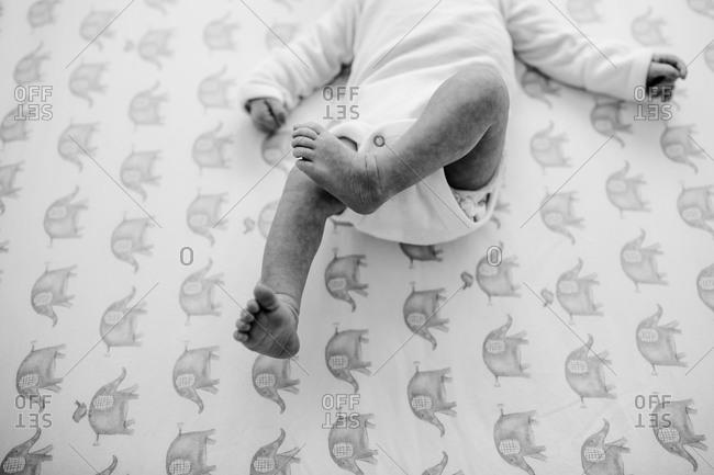 Newborn baby's legs kicking on a elephant patterned sheet