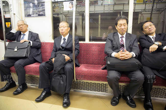 Tokyo, Japan - November 23, 2015: Businessmen on train in Tokyo