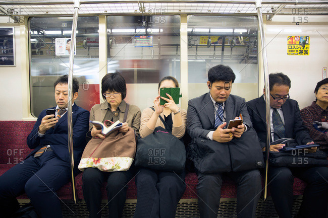Tokyo, Japan - November 23, 2015: People on devices in Tokyo train