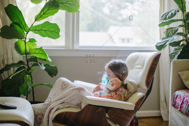 Young girl sitting in chair with blanket uses a nebulizer