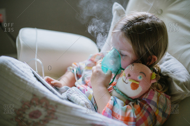 Close-up of young girl using a nebulizer while playing on tablet