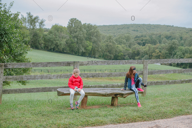 Two young girls sitting at opposite ends of a wooden bench
