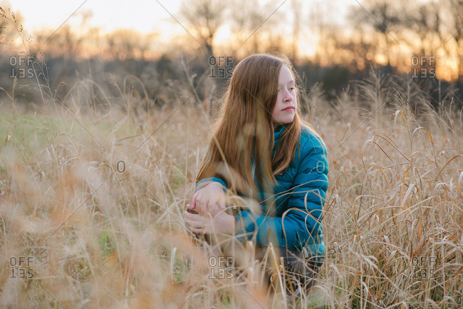 Portrait of a young girl sitting in field of dried grass at sunset