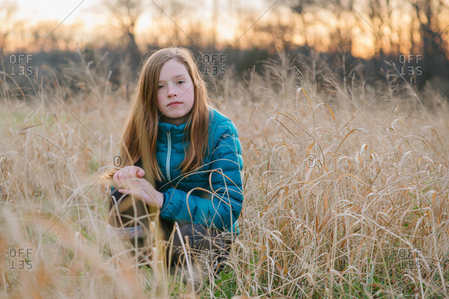 Portrait of a beautiful red haired girl in field at sunset