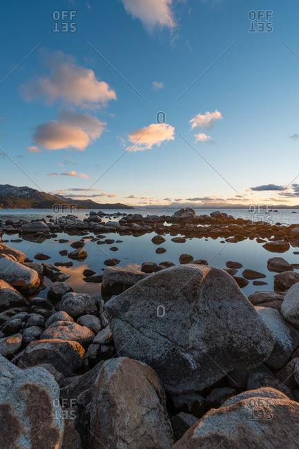Rocks along still ocean shore