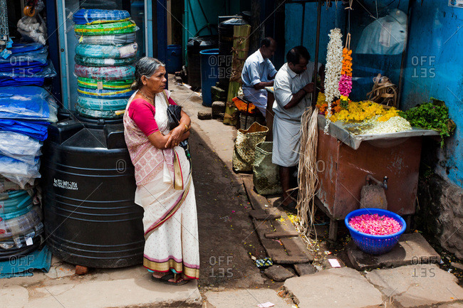 Kerala, India - September 10, 2013: Woman leaning against a water tank in a market in Kerala, India