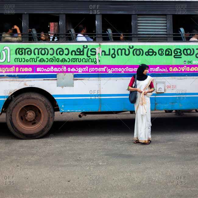 Kerala, India - September 11, 2013: Woman standing in front of a bus in the streets of Kerala, India