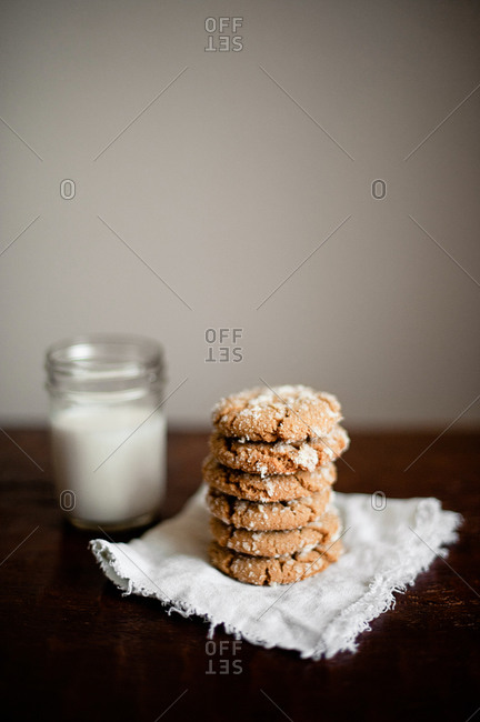 Stack of cookies with sugar crystals on linen table with jar of milk