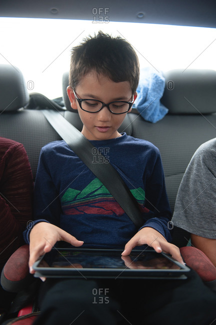 Young boy sitting in back seat and playing on tablet