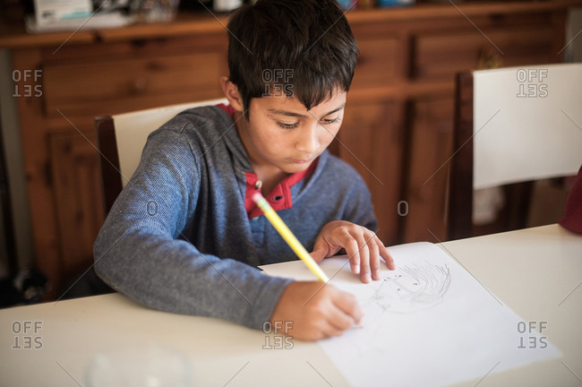 Young boy drawing at table with pencil