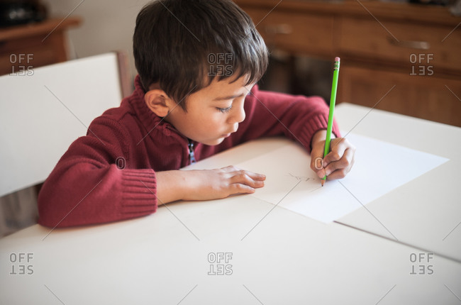 Young boy drawing with green pencil at table