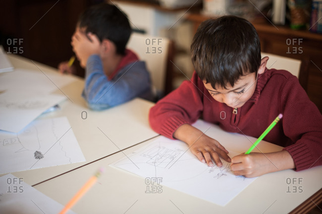 Two young boys drawing at table