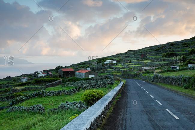 Barns and stone walls beside a road on Corvo Island, Portugal