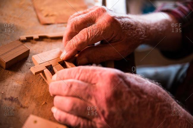 Hands of a man assembling a traditional door lock, Corvo Island, Portugal