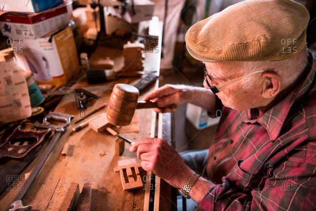 Corvo Island, Portugal - June 10, 2015: Senior man making a traditional door lock, Corvo Island, Portugal