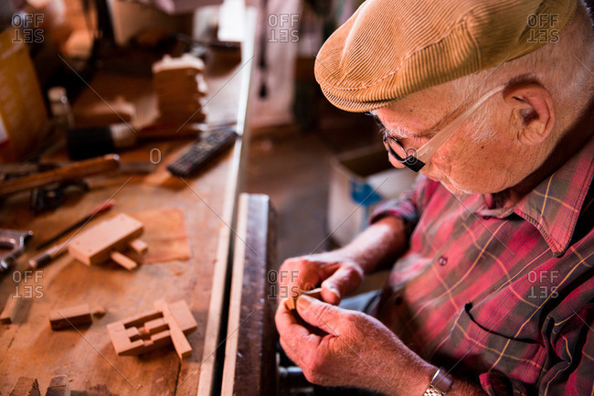 Corvo Island, Portugal - June 10, 2015: Senior man assembling a traditional door lock, Corvo Island, Portugal