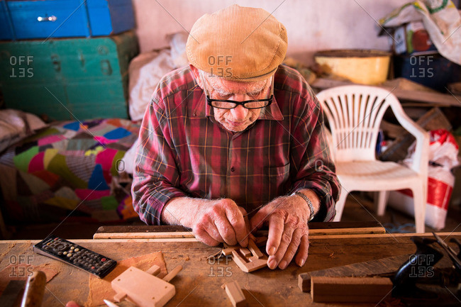 Corvo Island, Portugal - June 10, 2015: Senior man putting together a traditional door lock, Corvo Island, Portugal