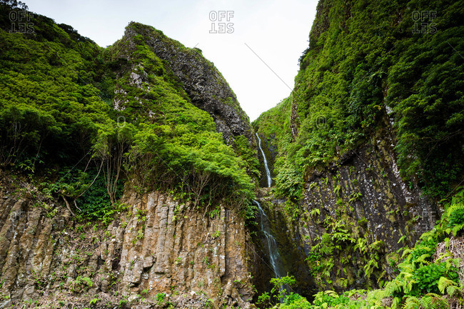 Waterfall between high cliffs at Flores Island, Portugal