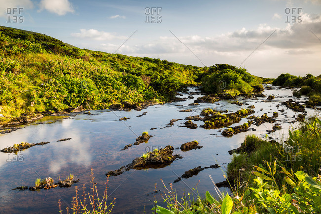 Ribeira Grande stream at the edge of a lush cliff on Flores Island, Portugal