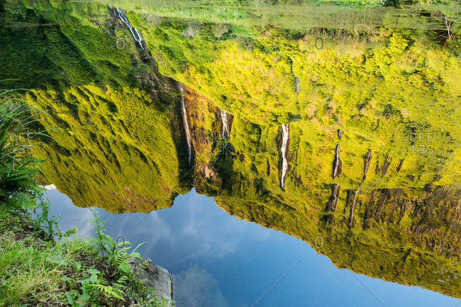 Reflection of Poco da Alagoinha waterfall in a pool of water, Flores Island, Portugal