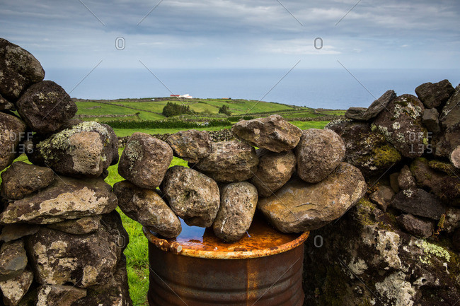 Metal barrel and stones used as a pasture gate on Corvo Island, Portugal