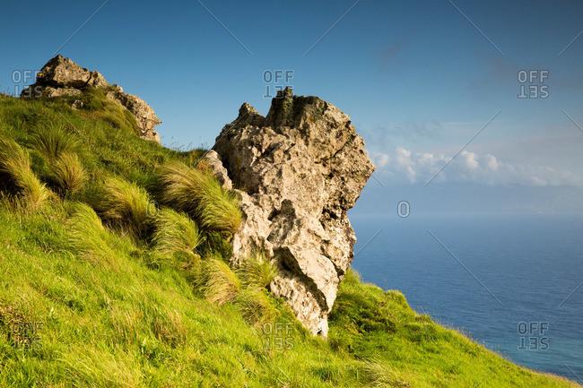 Rock formation on a grassy seaside cliff, Corvo Island, Portugal