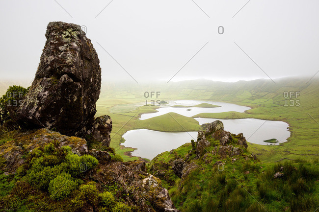 Mossy rocks on the rim overlooking the crater at Corvo Cauldron, Portugal