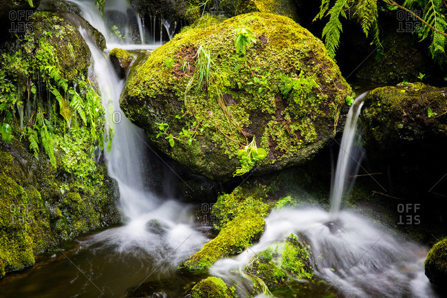 Small waterfall flowing over mossy rocks on Corvo Island, Portugal