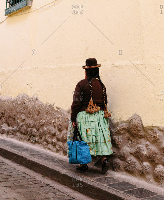 Native woman on the sidewalk in Peru