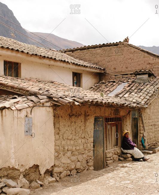 Ollantaytambo, Peru - September 2, 2015: Elderly woman sitting outside a house