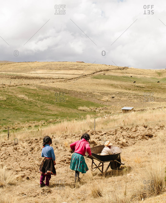 Tinki, Peru - September 4, 2015: Children playing with a wheelbarrow in Tinki, Peru