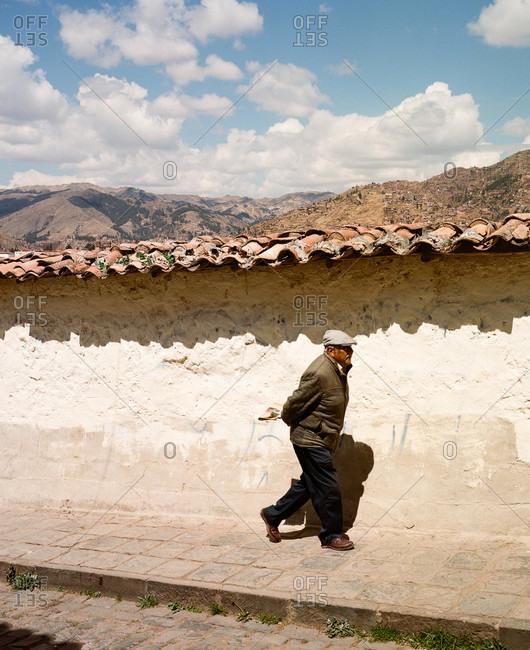 Cusco, Peru - December 22, 2015: Man walking along sidewalk