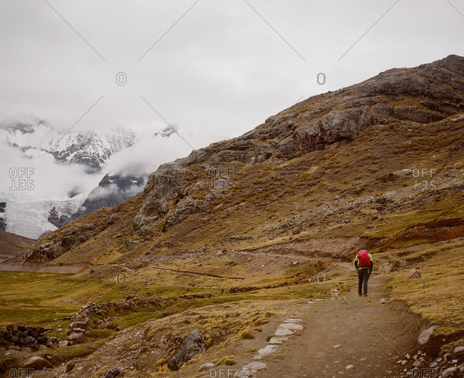 Hiker on a trail in Ausangate in the Andes Mountains of Peru