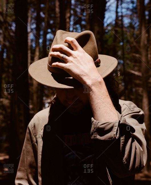 Man adjusting his hat in a coastal forest in California